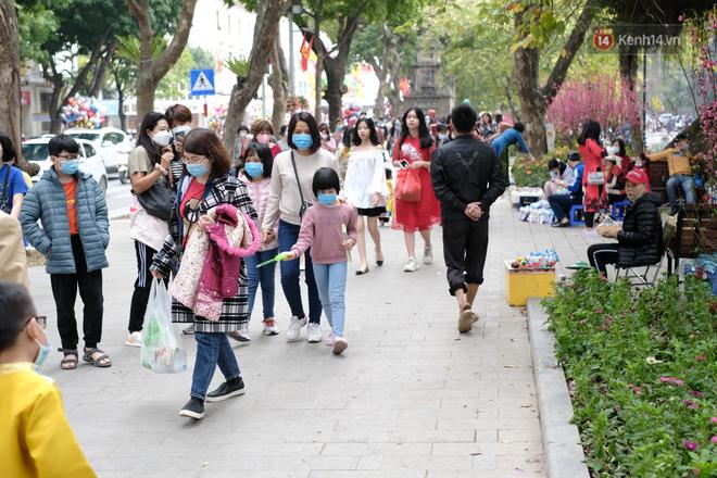 Chùm ảnh: Người dân đeo khẩu trang phòng dịch, xúng xính váy áo xuống phố dạo chơi chiều mùng 2 Tết