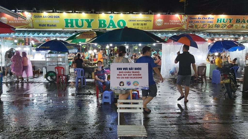 Thanh niên phát khẩu trang cho du khách tham quan chợ đêm Phú Quốc