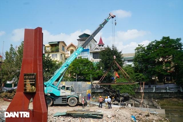 Cảnh cần cẩu nhấc bổng xác pháo đài bay B-52 dưới đáy hồ lên bờ ở Hà Nội