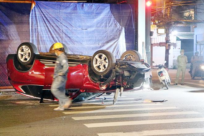 Ô tô lật ngửa sau khi húc bay cột đèn, 2 người bò ra khỏi xe cầu cứu
